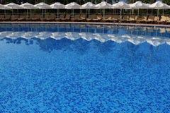 Έδρες και πισίνα ομπρελών πλησίον Στοκ φωτογραφία με δικαίωμα ελεύθερης χρήσης