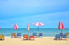 Έδρες και umbellar στην άσπρη παραλία άμμου Στοκ Φωτογραφία