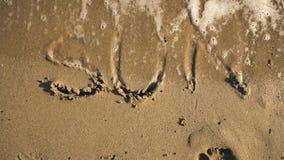 Ήλιος ` λέξης ` στην άμμο που πλένεται από την άποψη κυμάτων φιλμ μικρού μήκους