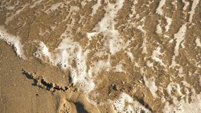 Ήλιος ` λέξης ` στην άμμο που πλένεται από το βίντεο κυμάτων απόθεμα βίντεο