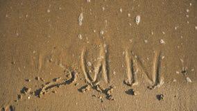 Ήλιος ` λέξης ` στην άμμο που πλένεται από το βίντεο κυμάτων φιλμ μικρού μήκους