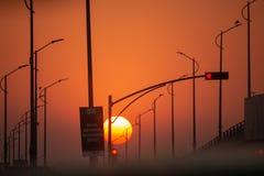 Ήλιος που θέτει στη μέση μιας κενής οδού στοκ εικόνα
