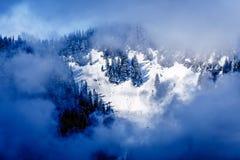 Ήλιος που λάμπει μέσω των σύννεφων στην καλυμμένη χιόνι αιχμή του βουνού Coquitlam στα βουνά ακτών Στοκ Εικόνα