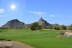 Ήλιος που λάμπει πέρα από μια πράσινη στενή δίοδο γκολφ με τα βουνά και έναν μπλε ουρανό στοκ φωτογραφία