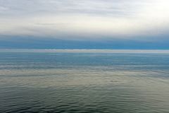 Ήρεμα νερά και απόμακρα σύννεφα σε μια ακτή λιμνών στοκ εικόνα με δικαίωμα ελεύθερης χρήσης