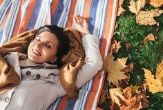 Ήρεμα χαμογελώντας γυναίκα που βρίσκεται στη χλόη στο πάρκο φθινοπώρου Στοκ φωτογραφία με δικαίωμα ελεύθερης χρήσης