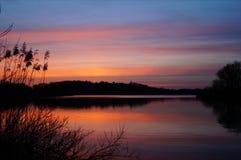 Ήρεμη λίμνη που απεικονίζει τον ουρανό ηλιοβασιλέματος Στοκ Φωτογραφίες