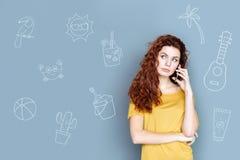 Ήρεμη γυναίκα που κρατά ένα τηλέφωνο και που μιλά σε έναν ταξιδιωτικό πράκτορα στοκ φωτογραφίες