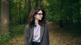Ήρεμη επιχειρηματίας στα γυαλιά που περπατά σε ένα δάσος φθινοπώρου απόθεμα βίντεο