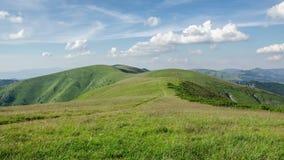 Ήρεμη ηλιόλουστη ημέρα στο πράσινο λιβάδι βουνών με το μπλε ουρανό και το άσπρο χρονικό σφάλμα σύννεφων φιλμ μικρού μήκους