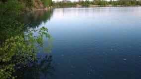 Ήρεμη και γαλήνια λίμνη βουνών με το αντανακλαστικούς νερό και το βράχο φιλμ μικρού μήκους