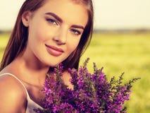Ήρεμη και χαλαρωμένη όμορφη γυναίκα υπαίθρια με τα λουλούδια στα χέρια στοκ εικόνες
