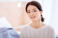Ήρεμη νέα γυναίκα στη θερμή συνεδρίαση πουλόβερ στο δωμάτιό της Στοκ Φωτογραφία