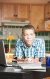 Ήρεμος έφηβος με τα βιβλία και υπολογιστής στον πίνακα Στοκ εικόνα με δικαίωμα ελεύθερης χρήσης