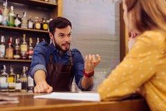 Ήρεμος μπάρμαν που εξετάζει τον επισκέπτη και που εξηγεί τις συνταγές των κοκτέιλ στοκ εικόνα