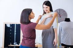 Ήρεμος ράφτης που φαίνεται σοβαρός συνεργαμένος με τον πελάτη της Στοκ Εικόνες