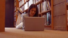 Ήρεμος σπουδαστής που χρησιμοποιεί το lap-top στη βιβλιοθήκη φιλμ μικρού μήκους