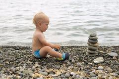 Ήρεμο μικρών παιδιών στην παραλία θάλασσας Χαριτωμένο αγοράκι που χαλαρώνει και που κοιτάζει στην πυραμίδα πετρών στοκ φωτογραφία με δικαίωμα ελεύθερης χρήσης