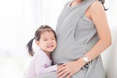 Ήχος ακούσματος κοριτσιών από την έγκυο κοιλιά μητέρων της ` s στοκ εικόνες