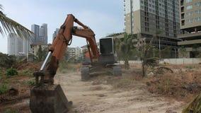Ήχος βιντεοσκοπημένων εικονών 1920x1080 αποθεμάτων Ο εκσκαφέας σε ένα εργοτάξιο οικοδομής εξισώνει το έδαφος καθαρίζοντας ένα εργ απόθεμα βίντεο