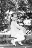 Ήχος και mp3 μουσικής Το μικρό κορίτσι ακούει μουσική στο θερινό πάρκο Το παιδί απολαμβάνει τη μουσική στα ακουστικά υπαίθρια Παι Στοκ Εικόνες