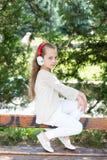 Ήχος και mp3 μουσικής Το μικρό κορίτσι ακούει μουσική στο θερινό πάρκο Το παιδί απολαμβάνει τη μουσική στα ακουστικά υπαίθρια Παι Στοκ εικόνες με δικαίωμα ελεύθερης χρήσης