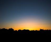 Ήλιος βραδιού που θέτει πίσω από μια σειρά των προαστιακών σπιτιών Στοκ Φωτογραφίες