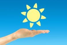 Ήλιος εικονιδίων σε ένα ανθρώπινο χέρι Στοκ Εικόνες