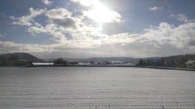 Ήλιος μέσω των σύννεφων σε έναν μπλε ουρανό με το χιόνι σε έναν τομέα Στοκ Εικόνες