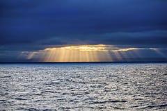 Ήλιος μέσω των σύννεφων στη θάλασσα Στοκ Εικόνα