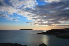 Ήλιος πίσω από τα σύννεφα επάνω από τη θάλασσα - επίπεδο στο χρόνο ηλιοβασιλέματος Στοκ εικόνα με δικαίωμα ελεύθερης χρήσης