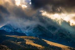 Ήλιος που λάμπει μέσω των σκοτεινών σύννεφων πέρα από τον αμμόλοφο άμμου βουνών Στοκ Εικόνες
