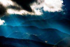 Ήλιος που λάμπει μέσω των σκοτεινών σύννεφων πέρα από τον αμμόλοφο άμμου βουνών Στοκ φωτογραφία με δικαίωμα ελεύθερης χρήσης