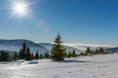 Ήλιος που λάμπει με τη φλόγα φακών πέρα από τα χιονισμένα γιγαντιαία βουνά Στοκ Φωτογραφίες