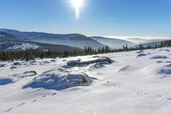 Ήλιος που λάμπει πέρα από τα χιονισμένα γιγαντιαία βουνά Στοκ Φωτογραφίες