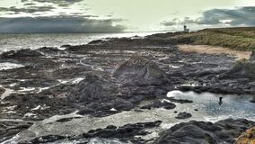 Ήλιος που εκρήγνυται πέρα από την παραλία βράχου Στοκ Φωτογραφία