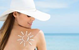 Ήλιος που επισύρεται την προσοχή στον ώμο της γυναίκας με την κρέμα προστασίας ήλιων