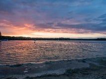 Ήλιος που θέτει πέρα από μια λίμνη στα ξύλα, στο καλοκαίρι Στοκ Εικόνες