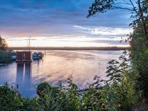 Ήλιος που θέτει πέρα από μια λίμνη στα ξύλα, στο καλοκαίρι Στοκ Εικόνα