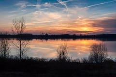 Ήλιος που θέτει πέρα από τον ποταμό Στοκ Εικόνα
