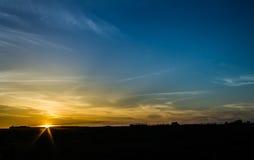 Ήλιος που θέτει πέρα από το λιβάδι αγελάδων Στοκ Φωτογραφία