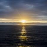 Ήλιος που θέτει στον ορίζοντα, που απεικονίζει ενάντια στην επιφάνεια της θάλασσας Στοκ Φωτογραφία