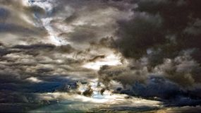 Ήλιος που προσπαθεί να κρυφοκοιτάξει από τα σκοτεινά σύννεφα Στοκ Φωτογραφία