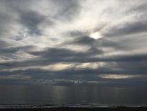 Ήλιος στα σύννεφα που απεικονίζουν στη θάλασσα Στοκ Εικόνα