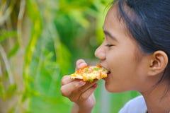 λίγο ταϊλανδικό κορίτσι με ένα σκοτεινό δέρμα που τρώει την πίτσα Στοκ εικόνα με δικαίωμα ελεύθερης χρήσης