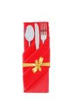 Δίκρανο, κουτάλι και μαχαίρι στο κόκκινο ύφασμα με το χρυσό τόξο που απομονώνεται στο W Στοκ Φωτογραφία