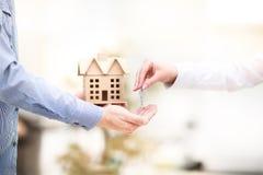 δίνοντας το σπίτι βασικός ά& Κλειδί με ένα keychain με μορφή του σπιτιού του στοκ φωτογραφίες