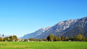 Ίντερλεικεν, Ελβετία, βουνά, σπίτια και τεράστιος τομέας ναυπηγείων χορτοταπήτων στοκ φωτογραφία με δικαίωμα ελεύθερης χρήσης