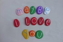 Ίσως σ' αγαπώ, χρωματισμένο κείμενο πετρών πέρα από την άσπρη άμμο στοκ φωτογραφία με δικαίωμα ελεύθερης χρήσης
