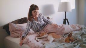 Ίχνη έφηβη επάνω στο κρεβάτι με το σκυλί κατοικίδιων ζώων της απόθεμα βίντεο